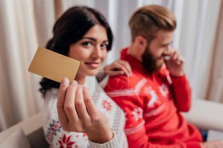 Photo pour Femme en pull d'hiver montrant carte de crédit tandis que l'homme parle par téléphone - image libre de droit