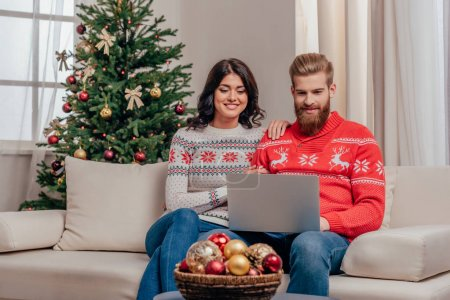 happy couple using laptop on christmas