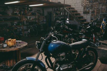 Photo pour Motos classiques debout dans l'atelier de réparation sombre - image libre de droit