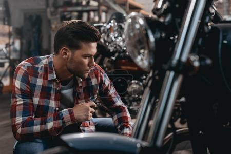 Photo for Young handsome biker with classic motorcycle in workshop - Royalty Free Image