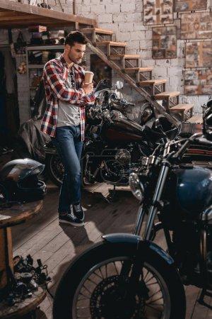 Man in repair shop with classic motorbikes