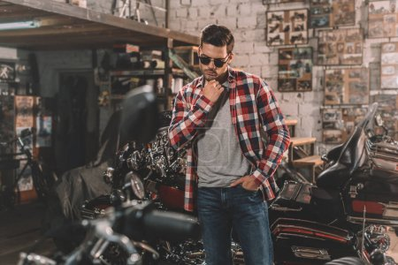 motorcyclist in sunglasses with motorbike