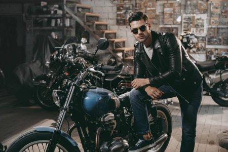 Photo pour Jeune motard beau en blouson de cuir noir avec des motos classiques en atelier - image libre de droit