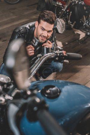Photo pour Jeune beau motard avec une moto classique en atelier - image libre de droit
