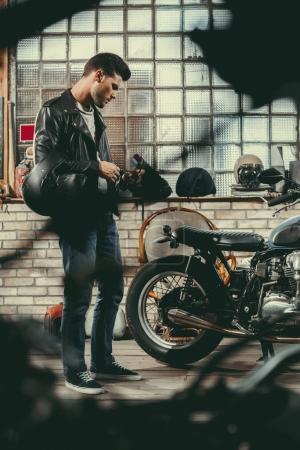 biker with motorcycle in workshop