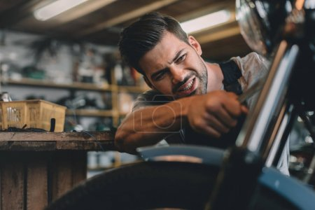 Photo for Young handsome professional automechanic fixing motorbike in workshop - Royalty Free Image