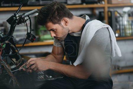 mechanic repairing motorbike