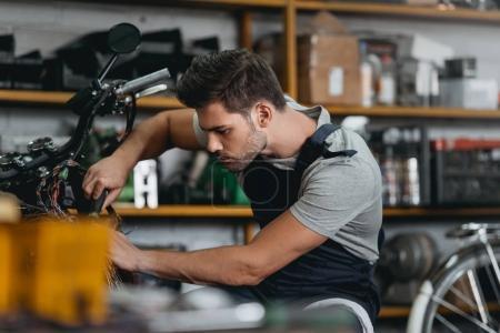 automechanic repairing motorbike
