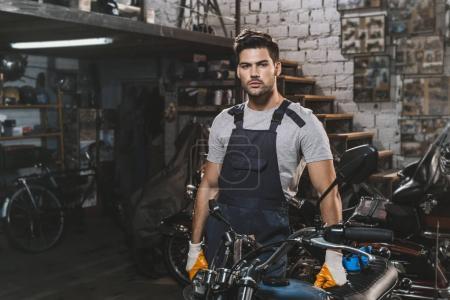 Photo pour Jeune beau mécanicien réparation moto en atelier - image libre de droit