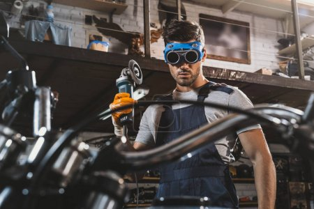 Mechanic with circular saw in workshop