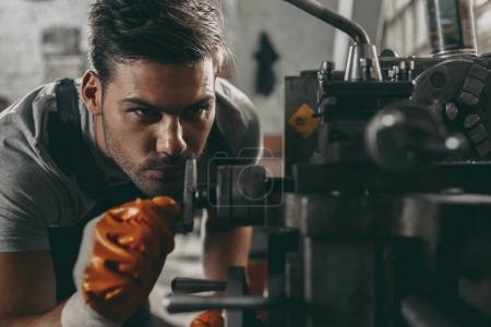 Photo for Young handsome mechanic working in workshop - Royalty Free Image