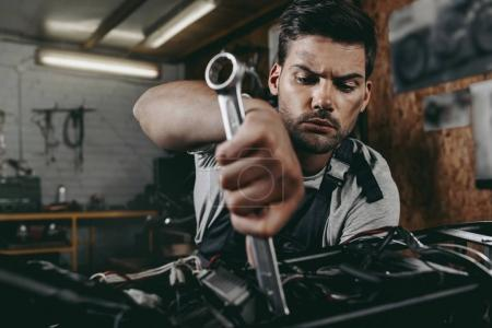 Photo for Young handsome mechanic repairing motorbike in workshop - Royalty Free Image