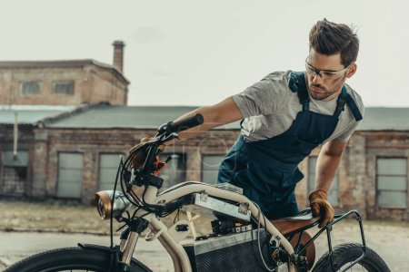 mechanic in goggles repairing motorcycle