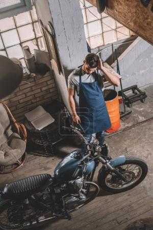mechanic with motorbike in garage