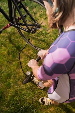 man pumping bicycle wheel