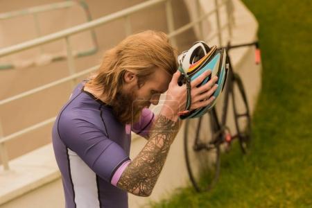 Photo pour Vue latérale du cycliste sérieux en tenue de sport portant un casque - image libre de droit