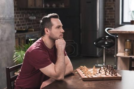 Photo for Handsome man sitting at table and thinking about making a move in chess - Royalty Free Image