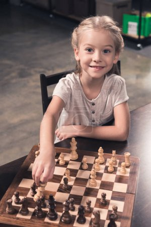 Preschooler child making move in chess