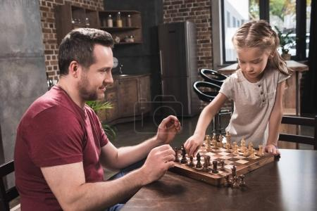 Daughter arranging chess pieces