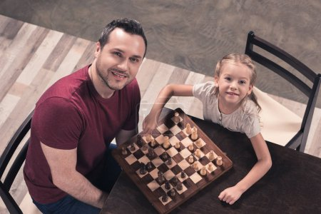 Father and daughter posing with chessboard