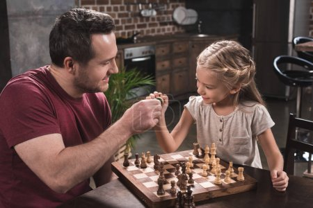 Father and daughter bumping chess pieces