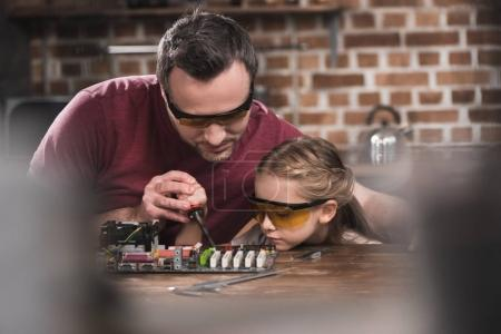 Photo for Father teaching daughter to braze, concentrated process - Royalty Free Image
