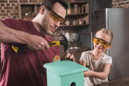 Daughter and father making birdhouse