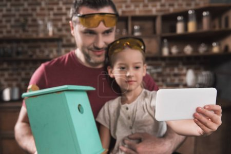 Photo for Father and daughter taking selfie with self-made birdhouse with smartphone at home - Royalty Free Image