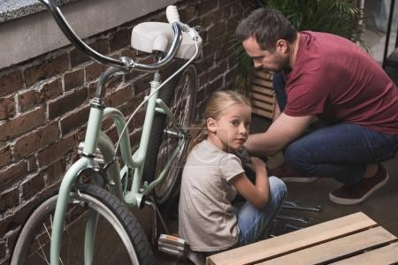 Father and daughter repairing bicycle