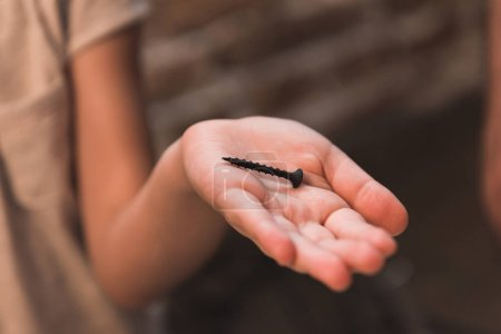 Photo for Cropped view of Preschooler child holding a screw in her hand - Royalty Free Image