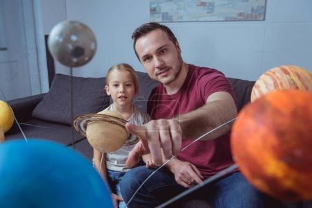 Photo pour Fille de père montrant une planète sur le modèle du système solaire - image libre de droit