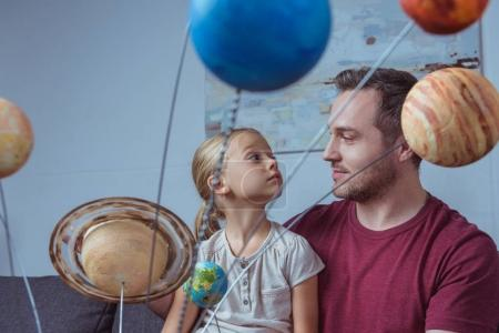 Father and daughter with planets model