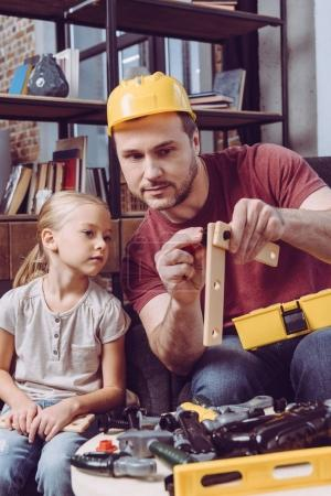 Father showing how make wooden frame