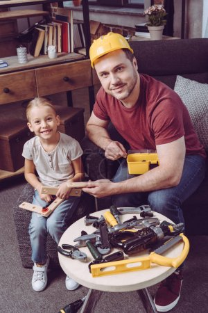 Father and daughter making wooden frame