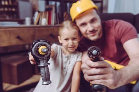 Father and daughter posing with toy drills