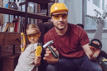 Father and daughter posing with plastic tools