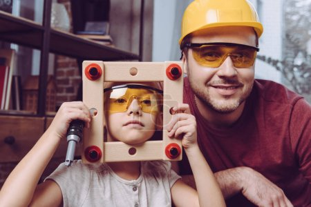 Father and daughter posing with self-made frame