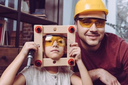 Photo for Father and daughter posing in yellow glasses with self-made wooden frame at home - Royalty Free Image