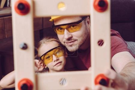 Photo for Father and daughter posing in yellow glasses with self-made wooden frame - Royalty Free Image