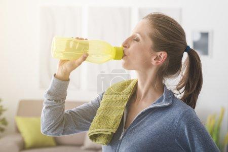 Photo pour Femme boire de l'eau à partir d'une bouteille après l'entraînement, concept de fitness et de sport - image libre de droit