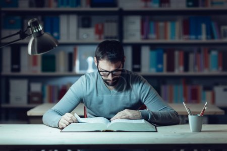 Photo pour Smart confiant jeune homme étudiant tard dans la nuit, il est assis au bureau et en lisant un livre - image libre de droit