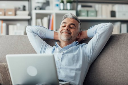 Photo for Happy businessman relaxing at home on the couch with a laptop on his lap, he is sleeping with hands behind head - Royalty Free Image