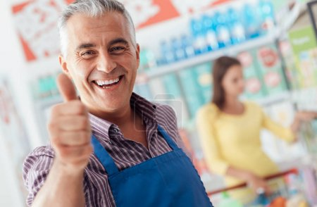 Supermarket clerk showing thumb up