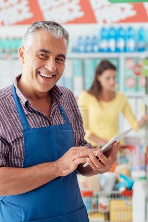 Supermarket clerk using tablet