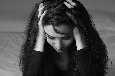 Photo for Desperate woman with head in hands, she is having an headache, depression and sadness concept - Royalty Free Image