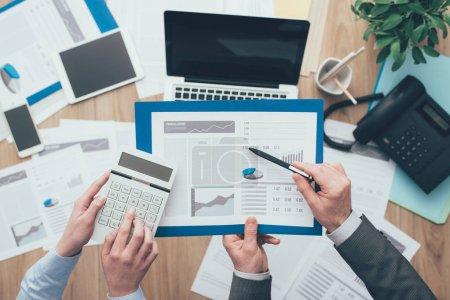 Photo pour Équipe d'affaires au travail, ils analysent certains rapports financiers et à l'aide d'une calculatrice, concept de finance et de comptabilité, vue de dessus - image libre de droit