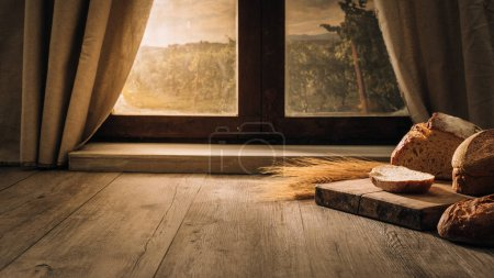 Photo for Fresh bread on the kitchen table in front of a window with a countryside panorama, healthy eating and traditional bakery concept - Royalty Free Image