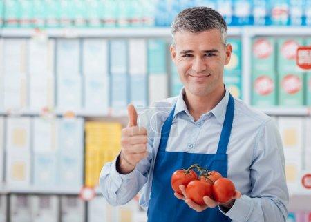 Photo pour Employé de supermarché tenant des tomates biologiques fraîches et donnant un pouce vers le haut, fraîcheur et concept alimentaire de qualité supérieure - image libre de droit