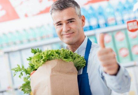 Photo pour Employé de supermarché professionnel tenant un sac d'épicerie avec des légumes frais et donnant un pouce vers le haut, fraîcheur et concept de contrôle de qualité - image libre de droit
