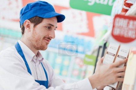 supermarket clerk working in store aisle